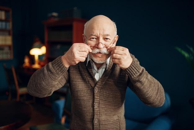 Un homme âgé gai montre sa moustache au bureau à domicile. senior mature barbu pose dans le salon, homme d'affaires de la vieillesse