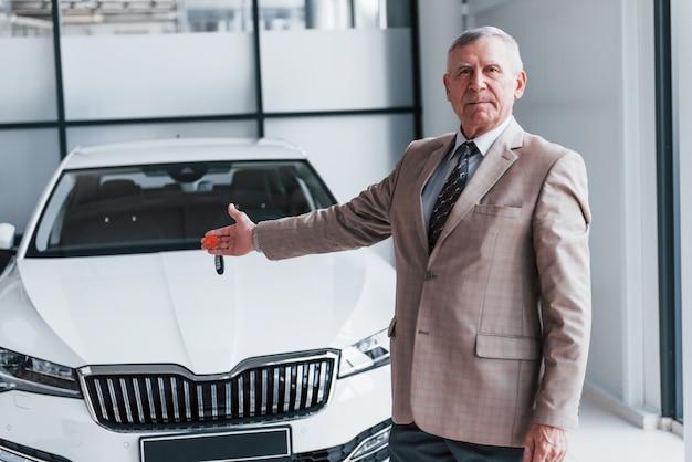 Un homme âgé gai en tenue de soirée se tient devant une voiture blanche moderne.