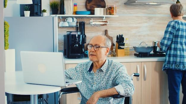 Homme âgé handicapé en fauteuil roulant travaillant sur un ordinateur portable dans la cuisine pendant que sa femme cuisine. homme d'affaires handicapé. paralysie d'un entrepreneur handicapé pour un homme retraité âgé