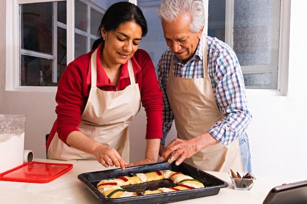 Un homme âgé et une jeune femme décorant de la pâte sur un plateau en métal pour faire du pain dans une cuisine, tous deux portant des tabliers