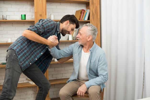 Homme âgé et jeune homme heureux avec les mains jointes dans la chambre