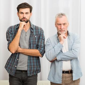 Homme âgé et jeune homme avec les mains près du menton