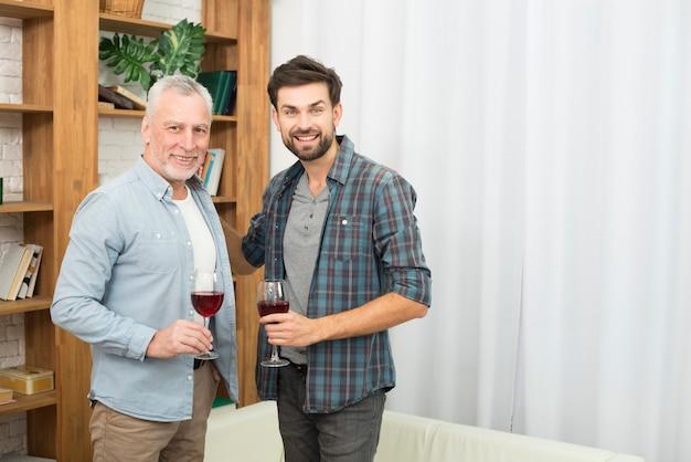 Homme âgé et jeune homme souriant avec des verres de vin près du canapé