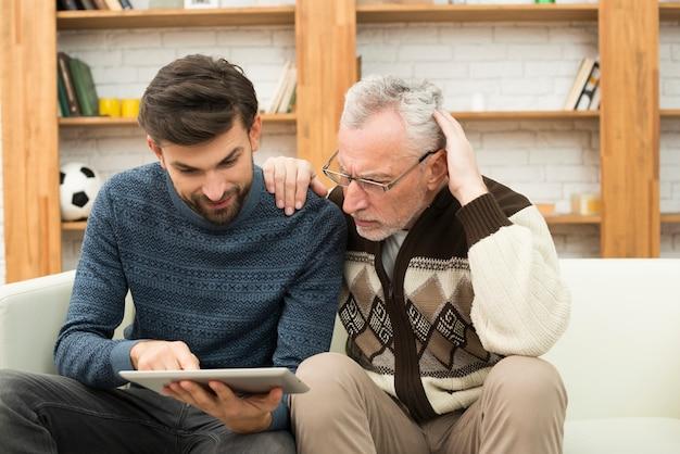 Homme âgé avec la main sur l'épaule du jeune homme à l'aide d'une tablette sur le canapé