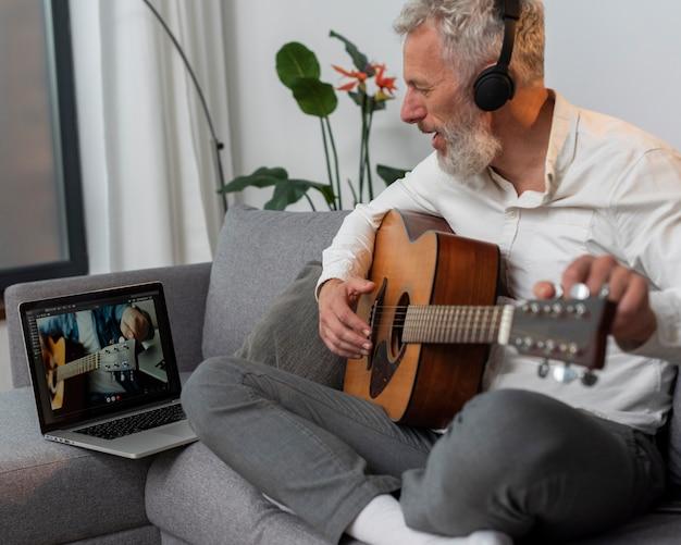 Homme âgé à la maison sur le canapé à l'aide d'un ordinateur portable pour étudier des cours de guitare
