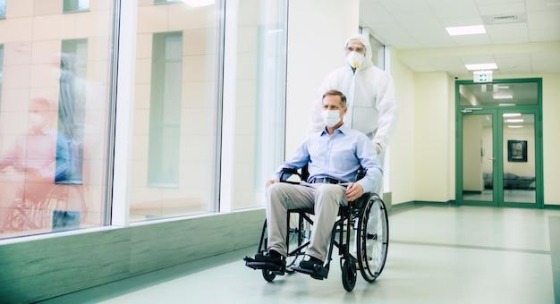 Homme âgé malade avec masque de protection sur le visage dans un fauteuil roulant et un médecin confiant dans le masque médical lors du transport à l'hôpital.