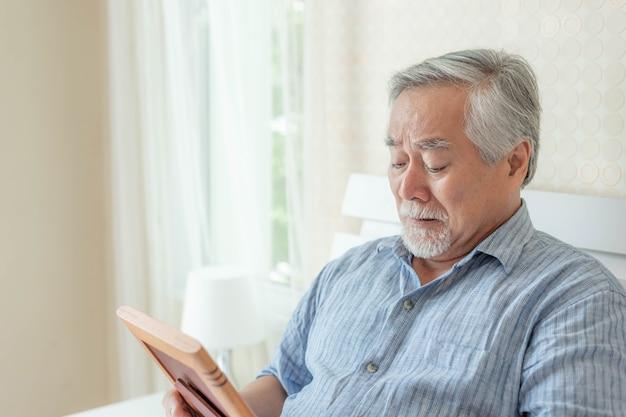 Un homme âgé malheureux pleure, étreint l'image de la femme décédée, souviens-toi de son amant de femme - concept senior tristement