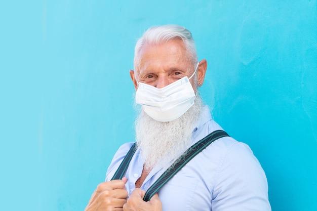Un homme âgé en masque contre un mur bleu lors d'une épidémie de coronavirus