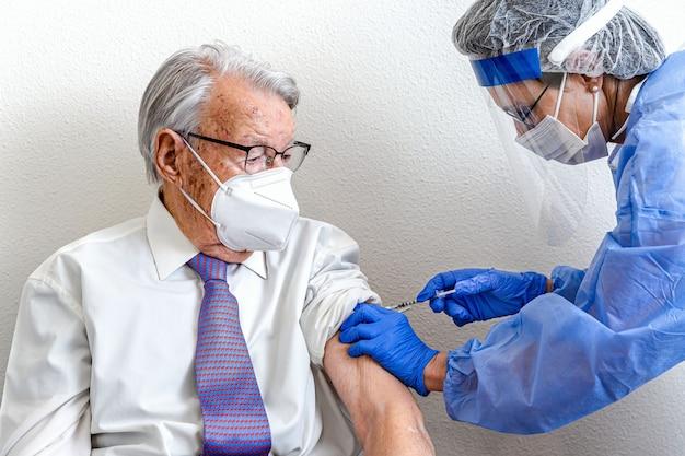 Un homme âgé en masque regarde une infirmière en tenue de protection et un masque covid lui donne le vaccin contre le coronavirus