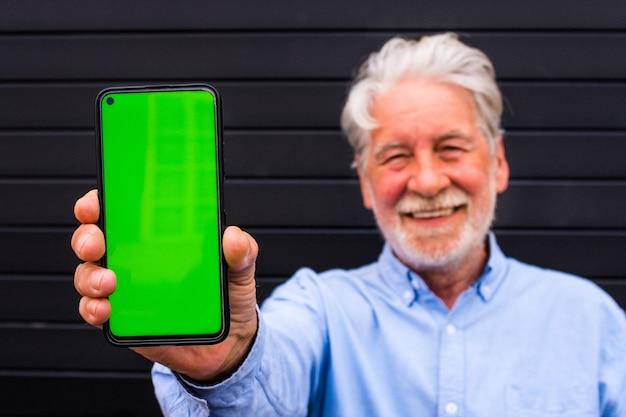 Un homme âgé et mature tenant un téléphone portable avec écran vert et le montrant à l'appareil photo