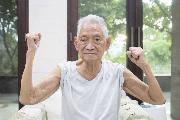 Un homme âgé montre sa force en levant le poing et le bras