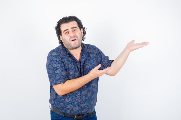 Homme d'âge moyen accueillant quelque chose en chemise et à la jolie vue de face.