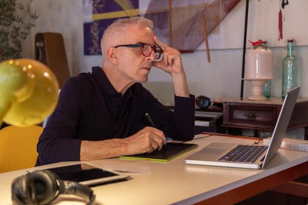 Homme d'âge moyen à l'aide d'ordinateur dans son studio d'art et dessin sur sa tablette