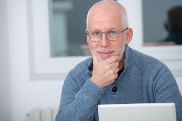 Homme d'âge moyen à l'aide d'un ordinateur portable dans son bureau