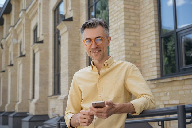 Homme d'âge moyen à l'aide de smartphone, internet, debout dans la rue