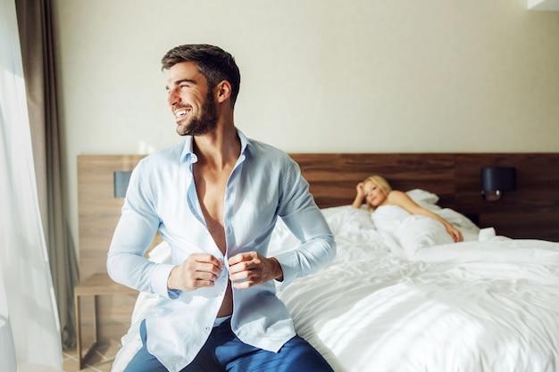 Un homme d'âge moyen assis sur le lit dans un hôtel et boutonnant sa chemise.