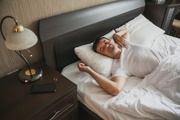 Un homme d'âge moyen au lit dans sa chambre se réveille le matin avec un sourire sur son visage. le concept de sommeil sain.