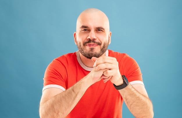 Un homme d'âge moyen avec une barbe dans un t-shirt rouge sur fond bleu se tient les bras tendus et se réjouit de la victoire. isolé.