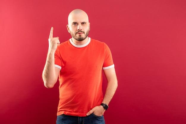 Un homme d'âge moyen avec une barbe dans un t-shirt rouge sur fond rouge montre joyeusement le haut. isolé.