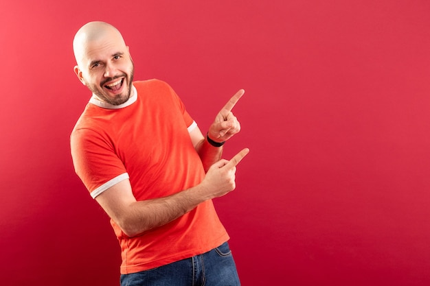 Un homme d'âge moyen avec une barbe dans un t-shirt rouge sur fond rouge pointe joyeusement vers la droite. isolé.