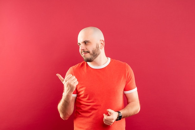 Un homme d'âge moyen avec une barbe dans un t-shirt rouge sur fond rouge pointe joyeusement vers la gauche. isolé.