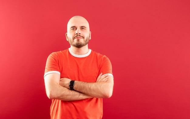 Un homme d'âge moyen avec une barbe dans un t-shirt rouge sur fond rouge se réjouit de la victoire. isolé.