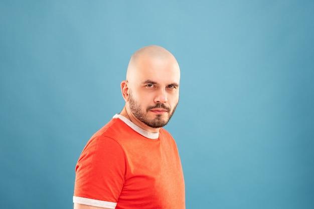 Un homme d'âge moyen avec une barbe dans un t-shirt rouge sur un mur bleu se tient les bras tendus et se réjouit de la victoire. isolé.