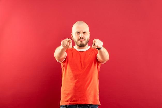 Un homme d'âge moyen avec une barbe dans un t-shirt rouge sur un mur rouge se réjouit de la victoire. isolé.