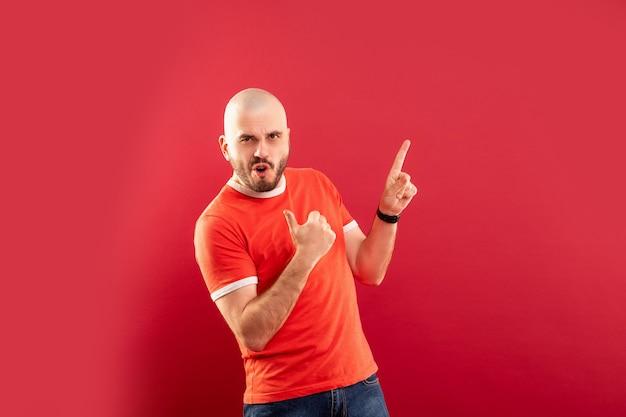 Un Homme D'âge Moyen Avec Une Barbe Dans Un T-shirt Rouge Sur Un Mur Rouge Se Réjouit De La Victoire. Isolé. Photo Premium