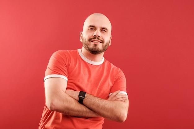 Un homme d'âge moyen avec une barbe dans un t-shirt rouge posant avec les bras croisés