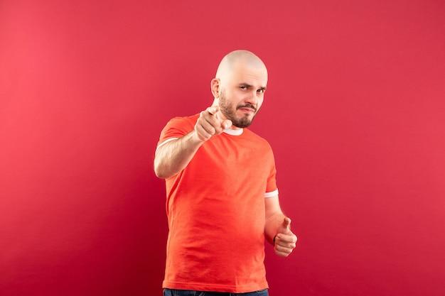 Un homme d'âge moyen avec une barbe dans un t-shirt rouge se réjouit de la victoire. isolé.