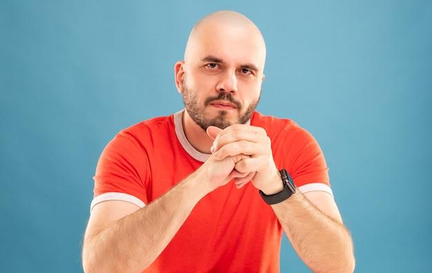 Un homme d'âge moyen avec une barbe dans un t-shirt rouge se tient les bras tendus et se réjouit de la victoire. isolé.