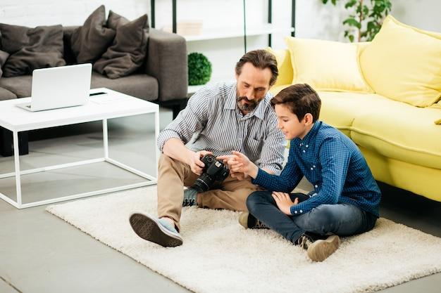 Homme d'âge moyen barbu assis sur le tapis à la maison avec son fils adolescent et lui montrant un nouvel appareil photo