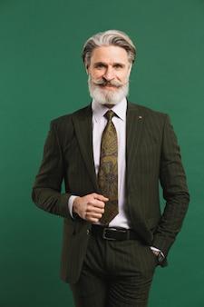 Homme d'âge moyen barbu élégant en costume sur le mur vert