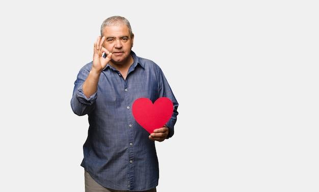 Homme âgé moyen célébrant la saint valentin gai et confiant faisant geste ok
