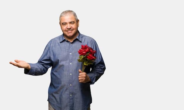Homme âgé moyen célébrant la saint-valentin tenant quelque chose avec la main
