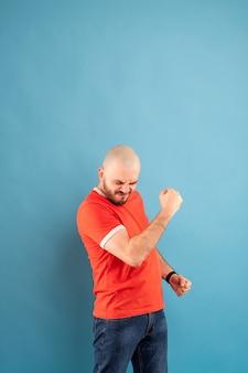 Un homme d'âge moyen chauve avec une barbe dans un t-shirt rouge sur fond bleu se tient les bras tendus et se réjouit de la victoire. isolé.