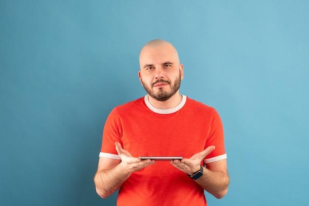 Un homme d'âge moyen chauve avec une barbe et un t-shirt rouge sur fond bleu. tient un téléphone dans sa main et le montre du doigt de l'autre main.