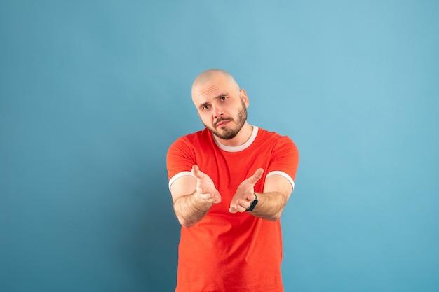 Un homme d'âge moyen chauve avec une barbe et un t-shirt rouge. montre ses paumes vers le spectateur. montre que ses mains sont vides.