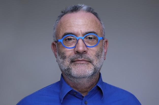 Homme d'âge moyen avec une chemise bleue et des lunettes