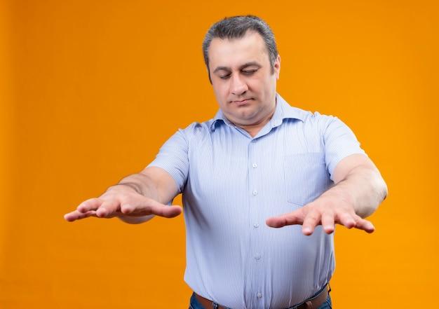 Homme d'âge moyen en chemise rayée bleue avec les yeux fermés essayant de trouver quelque chose en se tenant debout sur un fond orange
