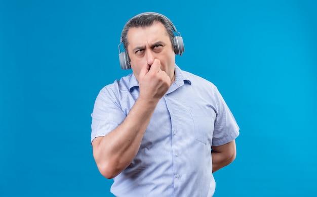 Homme d'âge moyen concentré en chemise à rayures bleues pensant à quelque chose tenant les doigts sur le nez sur un espace bleu