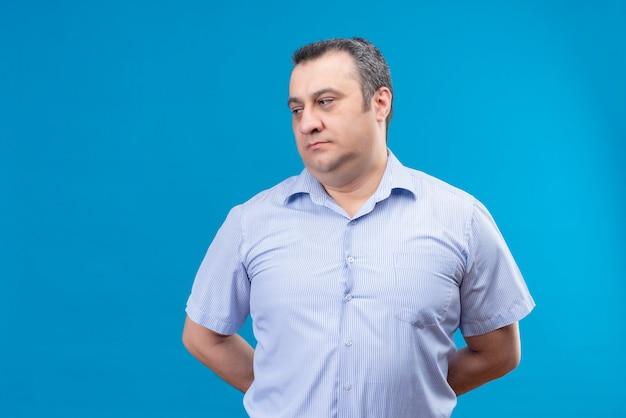 Homme d'âge moyen confus en chemise rayée bleue pensant mettre les mains sur le dos sur un espace bleu