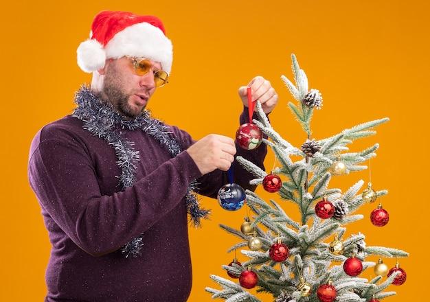 Homme d'âge moyen confus portant bonnet de noel et guirlande de guirlandes autour du cou avec des lunettes debout en vue de profil près de sapin de noël le décorant avec des boules de noël isolé sur fond orange