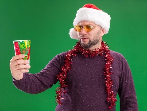 Homme d'âge moyen confus portant bonnet de noel et guirlande de guirlandes autour du cou avec des lunettes qui s'étend de la tasse de noël en plastique