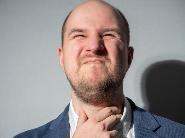 Un homme d'âge moyen en costume se tient la gorge. homme d'affaires, barbe, chauve, maladie, froid.