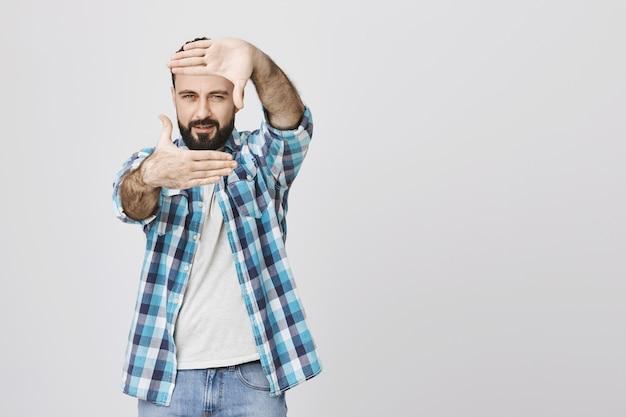 Homme d'âge moyen créatif faisant le plan, montrer le geste des cadres de la main
