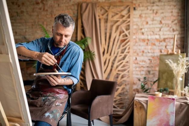Homme d'âge moyen créatif en tablier, mélange de couleurs sur palette avant de travailler sur une nouvelle peinture en studio