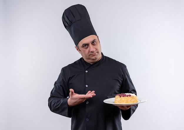 Homme d'âge moyen cuisinier en uniforme de chef montrant le gâteau sur une assiette à la main sur un mur blanc isolé