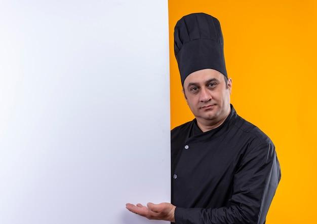 Homme d'âge moyen cuisinier en uniforme de chef montrant un mur blanc sur un mur jaune avec copie espace